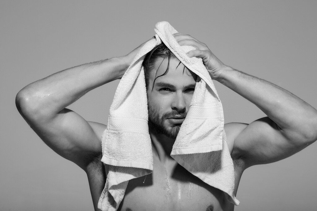 Wet topless man drying hair with white towel