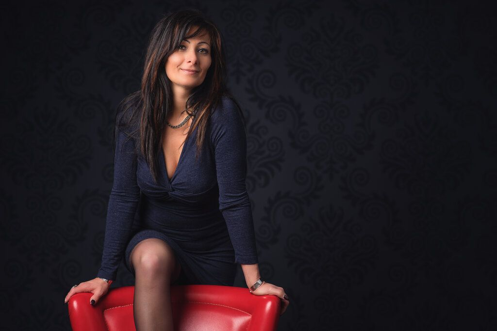 Seductive business woman in dark blue skirt on red armchair feeling horny and menopausal