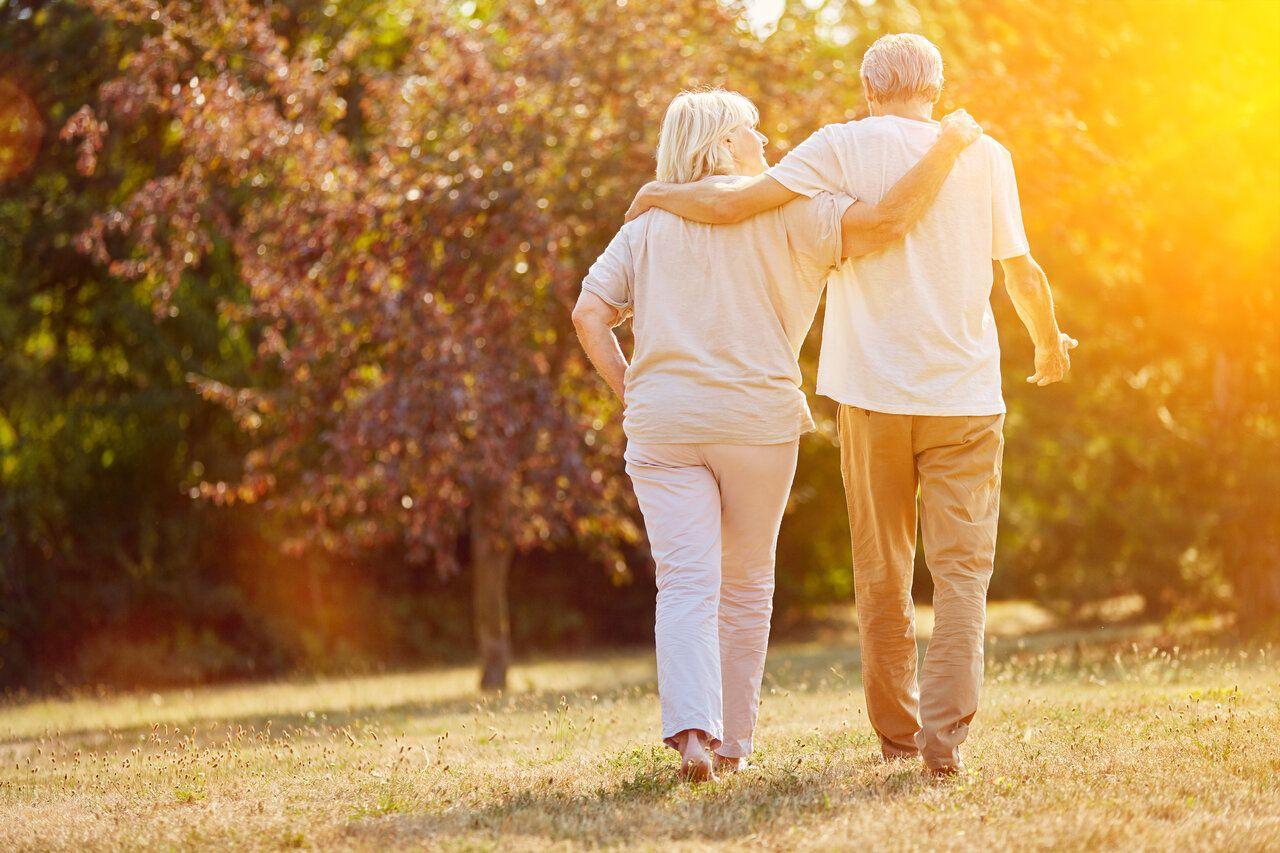 Senior couple walking towards trees and the sunset