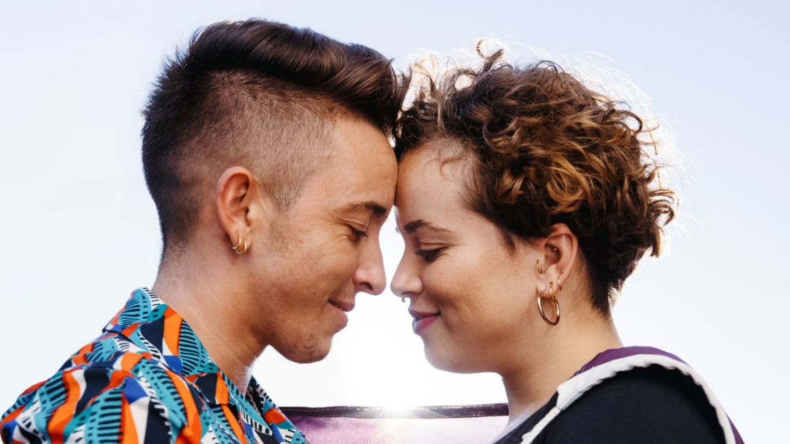 Image of trans couple looking at each other with love
