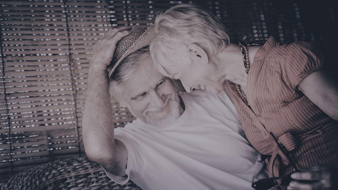 Older couple cuddling up on holiday thinking of senior sex
