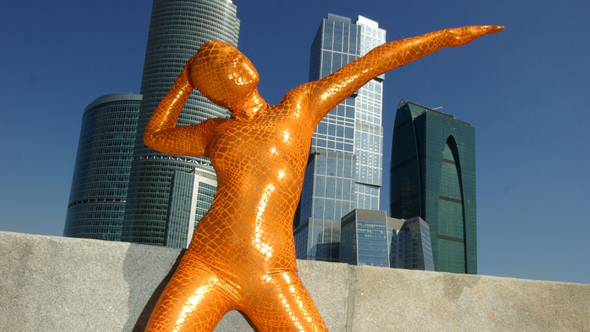 person in bright orange zentai suit near some skyscrapers pointing in the air whilst thinking about kink