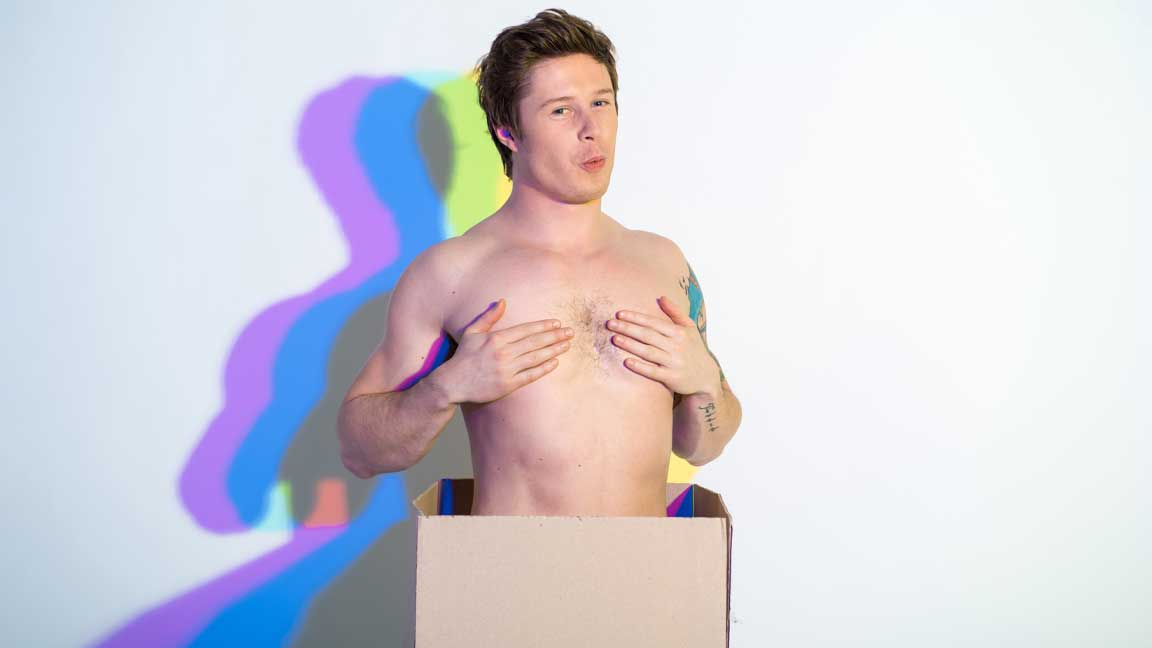 Cheeky topless guy poking out of cardboard box, covering his nipples