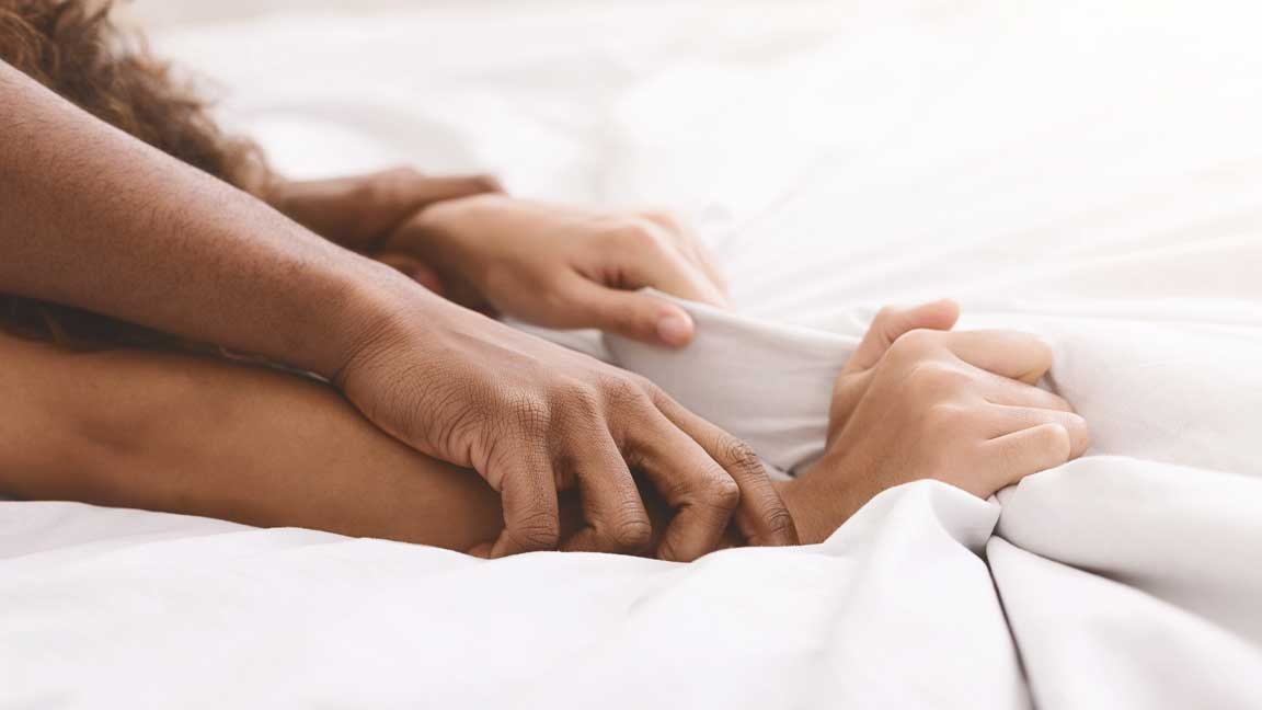 Couple in bed, holding wrists and gripping covers