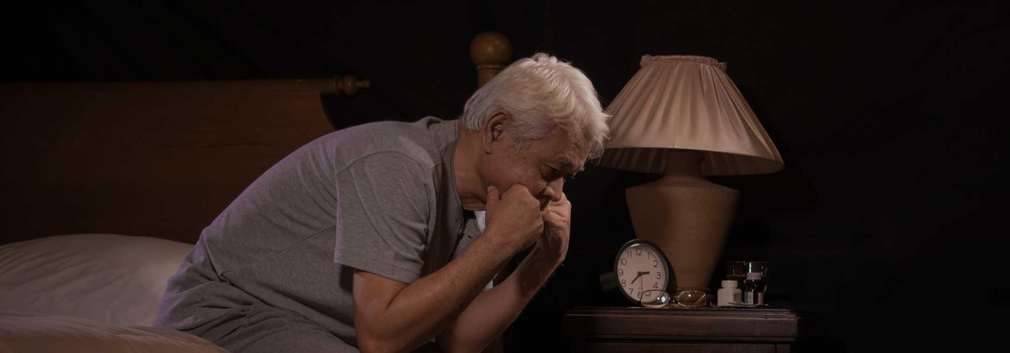 Depressed senior Asian man sitting on edge of the bed