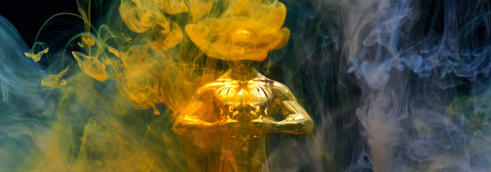 Gold statuette award surrounded by coloured smoke