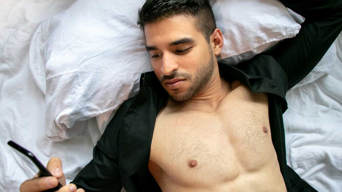 Man in bed wearing black shirt but open to show chest, holding phone