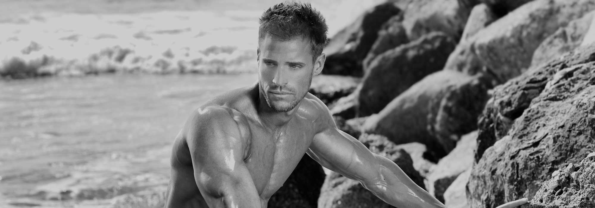 Muscular man at the beach, looking moody, black & white
