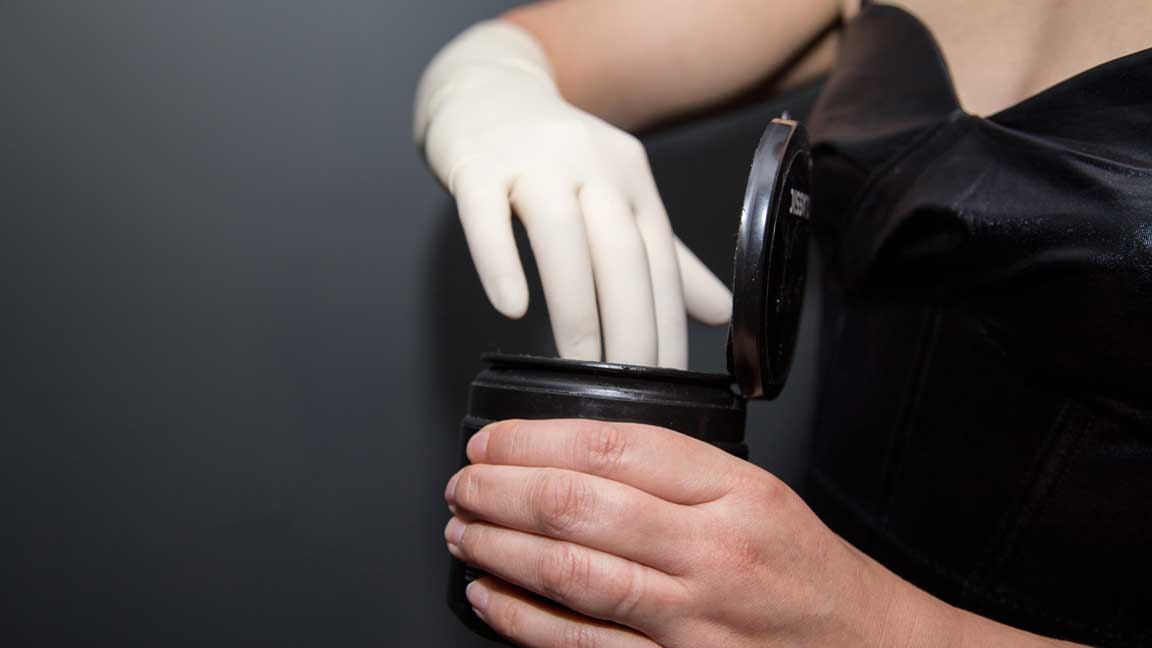 Woman with latex glove and black dress preparing to apply lube