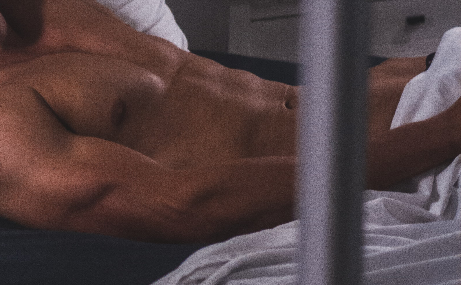 Topless muscular man reclining in bed with white bedsheets
