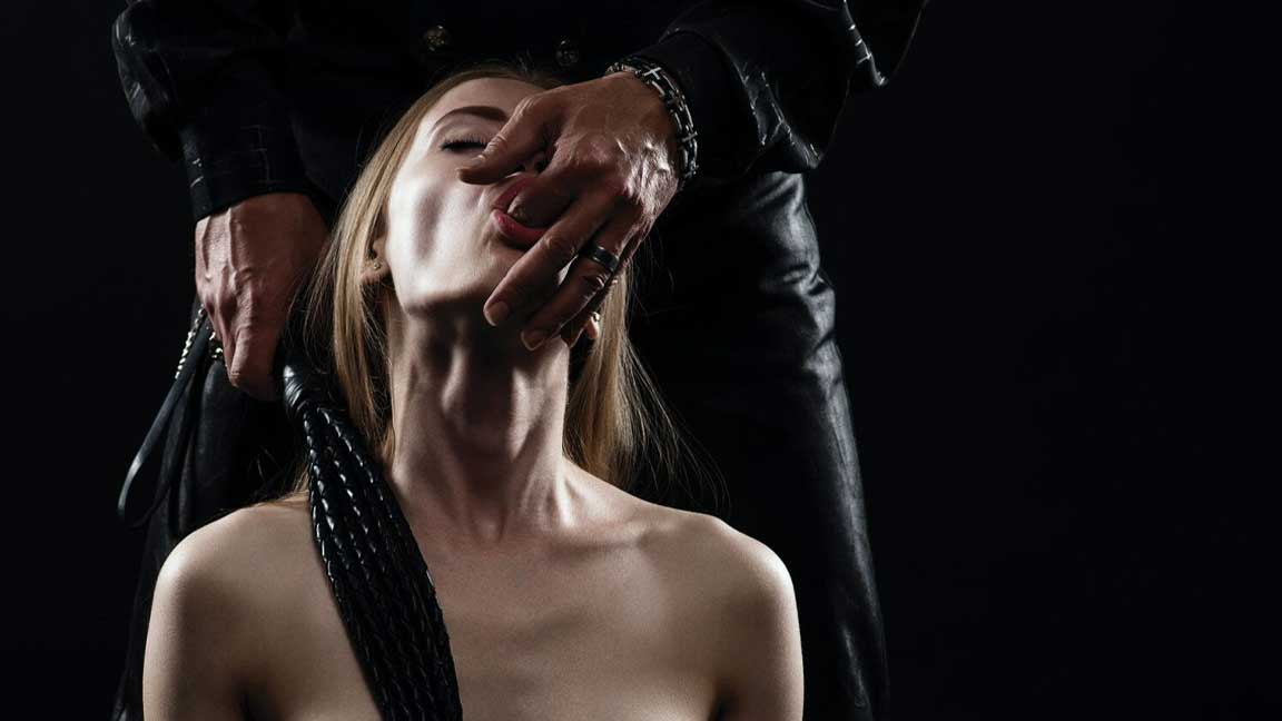 BDSM woman sucking finger suggestively, being dominated by man in black clothes standing behind her
