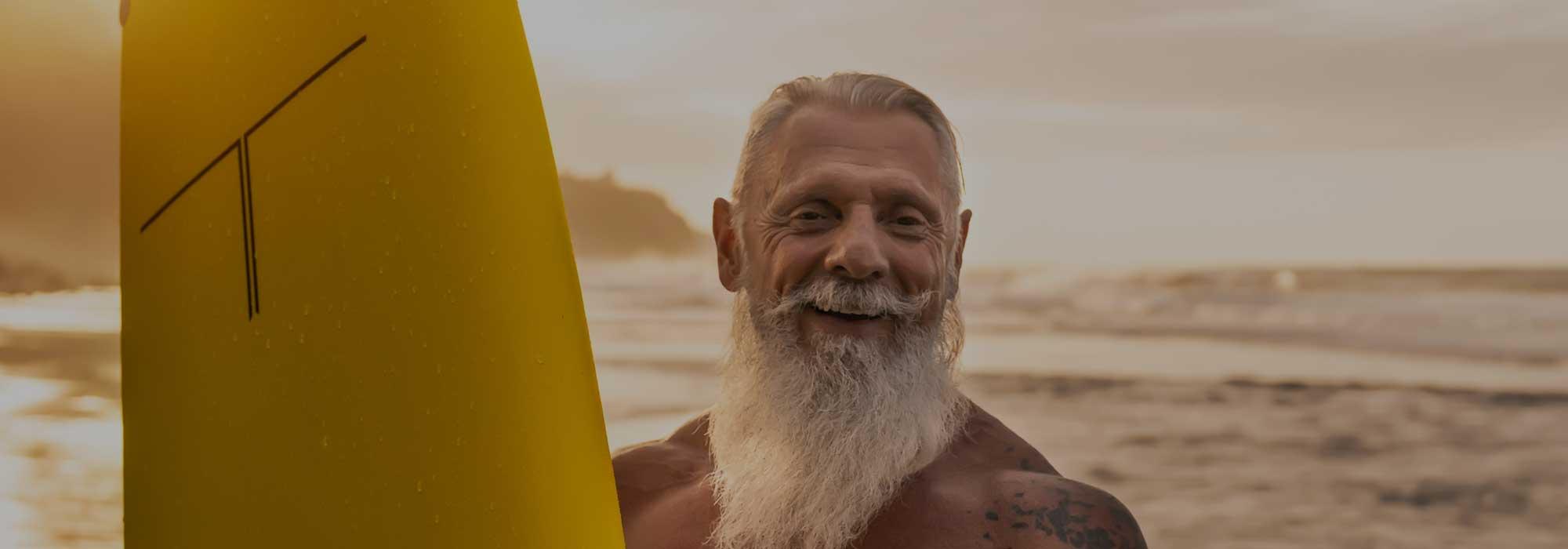 Senior bearded man at the sea holding yellow surfboard
