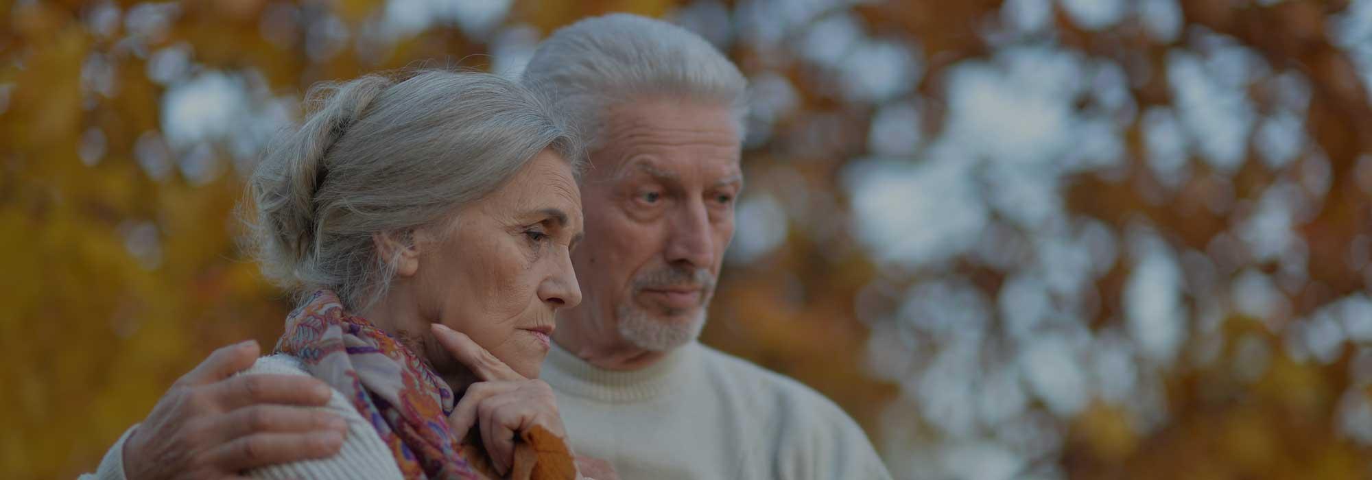 Senior couple stood outside looking unhappy