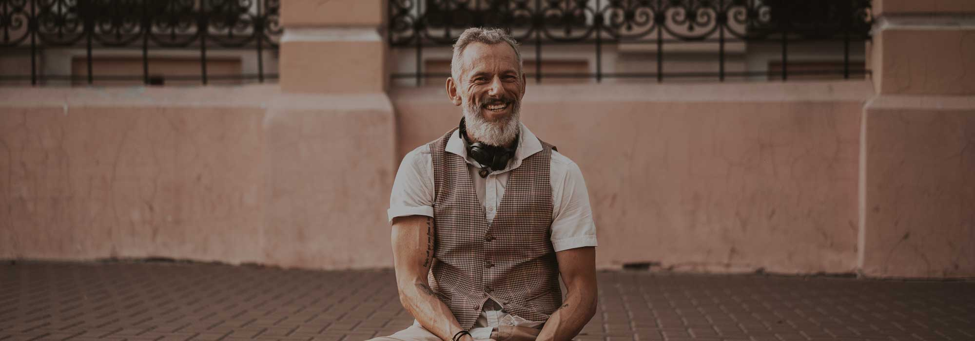 Senior bearded man smiling and sitting on skateboard in waistcoat and white shirt