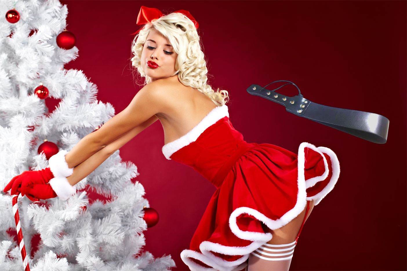 Sexy Mrs Claus by white Christmas tree, waiting to be spanked