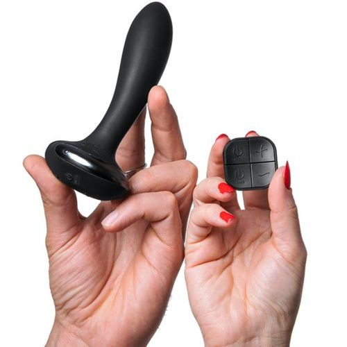 Anal Butt Plug shown held in male hand for scale and a femlae hand holding the remote control also for scale