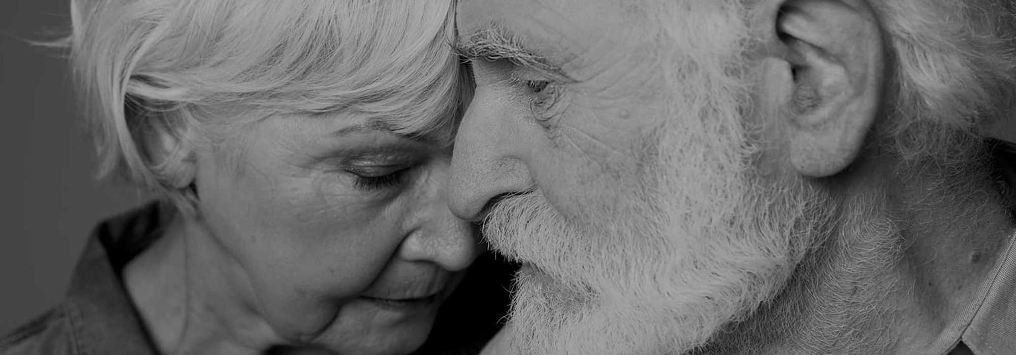 Sombre senior couple holding each other close in b&w